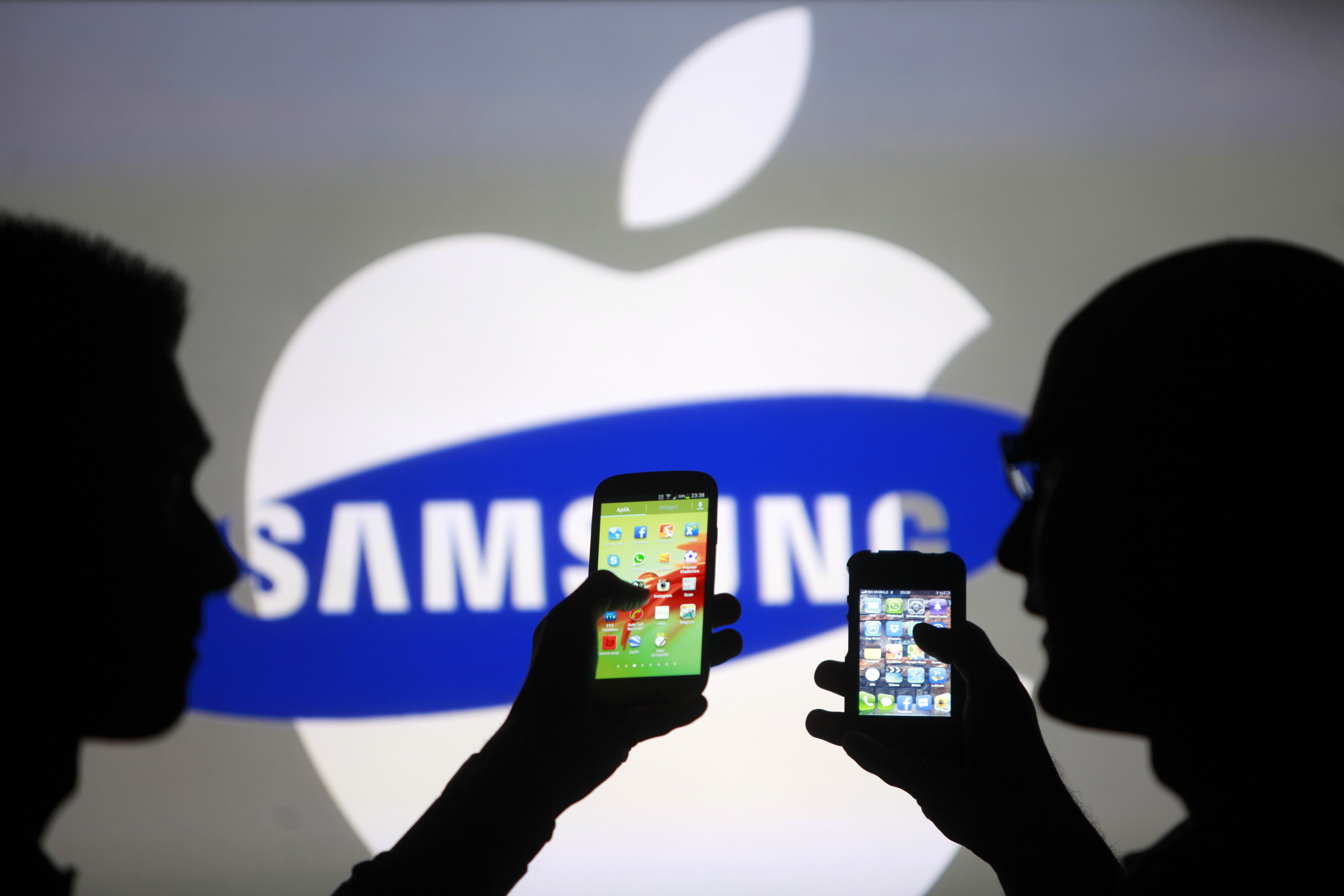 apple chiede 1 miliardo a samsung, foto silohuette di telefoni Galaxy e iPhone