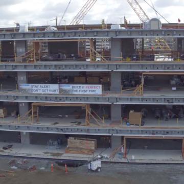 I quattro piani visibili in superfice sono stati completati; gli operai stanno sistemando le vetrate che saranno visibili dall'esterno.