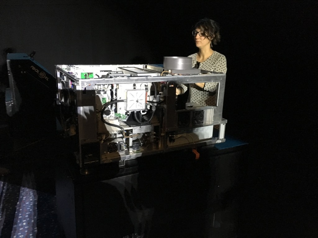Alice Tentori, Country Manager Italia di RealD) davanti ad un proiettore 3D per display da 20 metri: sulla sinistra è visibile in modulo RealD® XL Cinema per il recupero della luce