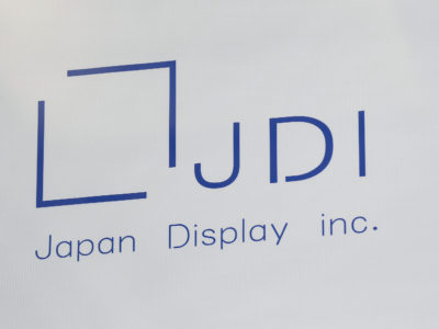 The Japan Display Inc. logo is seen on a replica of a glass panel used for liquid-crystal display (LCD) panels, displayed at the company's plant in Mobara, Chiba Prefecture, Japan, on Monday, March 17, 2014. Japan Display, a supplier of screens for Apple Inc. devices, and its investors will raise about 318.5 billion yen ($3.1 billion) after pricing its initial public offering at the bottom of the range. Photographer: Kiyoshi Ota/Bloomberg