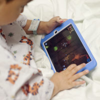 Axel Navarro, age 4, plays games on an iPad before his surgery at Lurie Children's Hospital in Chicago. The hospital is testing a new procedure with giving kids iPads to ease their surgery preparation and separation from parents. (PHOTO BY GREG RUFFING)