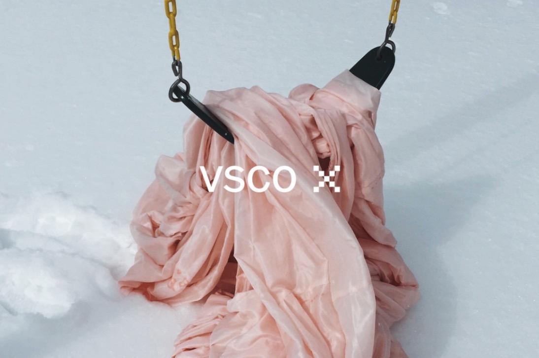 altalena con sopra veste rosa sulla neve e logo vsco x in sovraimpressione