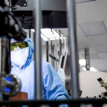Un tecnico di Finisar al lavoro su wafer di materiale semiconduttore durante la produzione