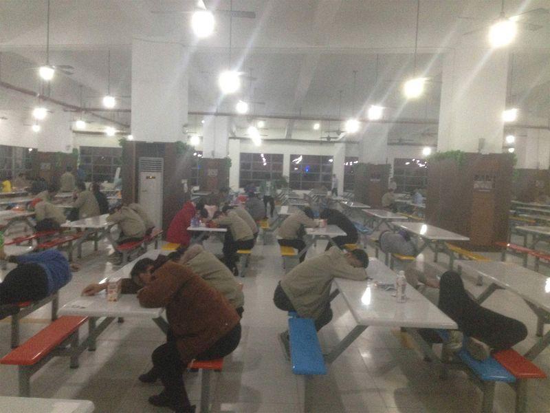 Operai che cerano di riposare durante una pausa, dormendo sui tavoli della caffetteria di Catcher