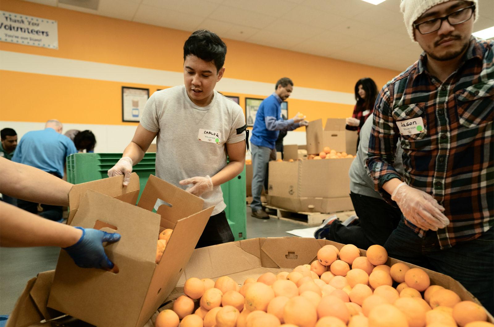 Volontari di Apple ripongono in una scatola delle arance presso la Second Harvest Food Bank di San Jose (California), organizzazione che contrasta lo spreco alimentare
