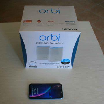 La confezione nella quale arriva il Sistema WiFi Orbi RBK50) vicino ad un iPhone XR